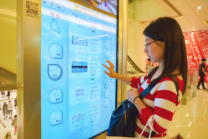 woman using headless commerce kiosk