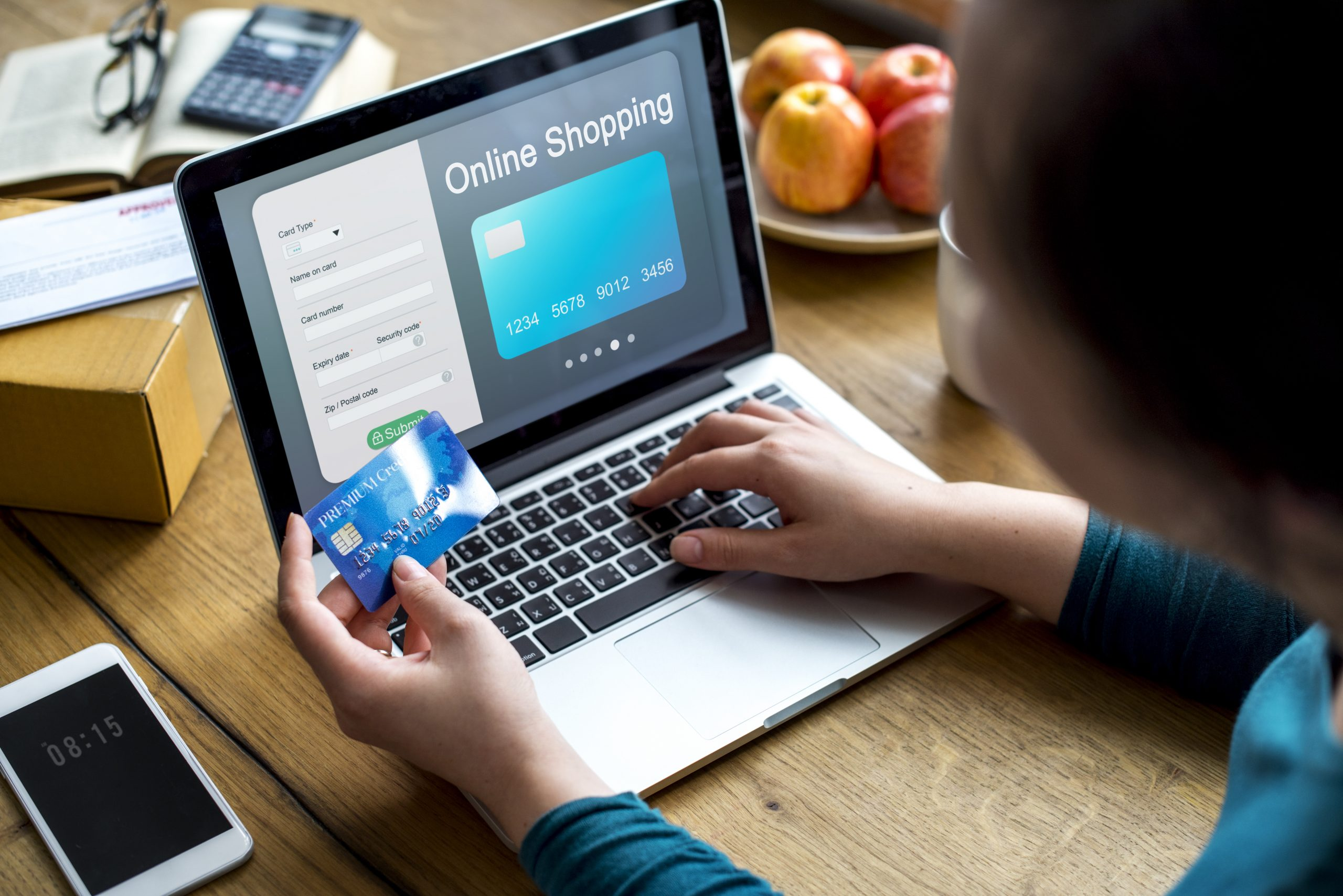 Hand holding credit card next to laptop displaying online store